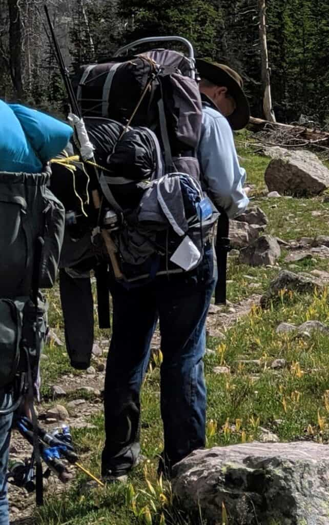 my-dad-wearing-jeans-with-a-big-packback-in-mountain-meadow