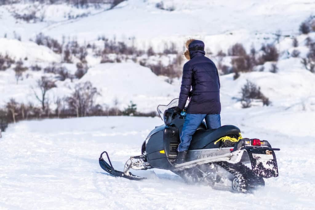 man-standing-on-snowmobile-over-snowy-landscape
