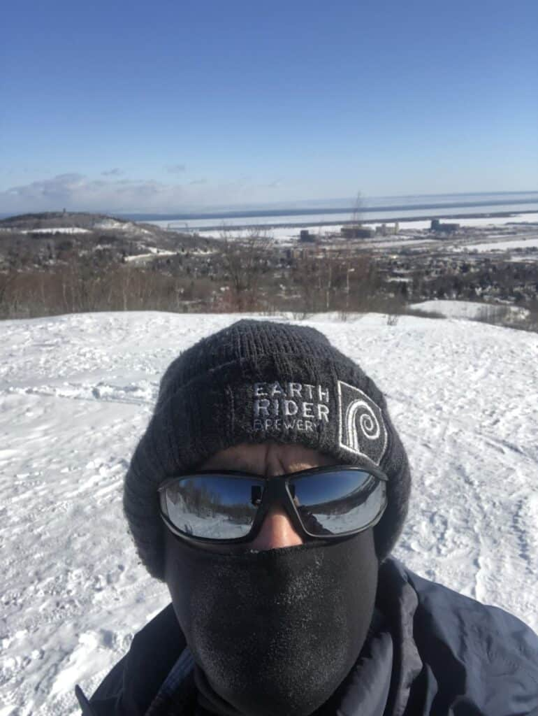 selfie-of-steve-standing-on-top-of-a-hill-while-he-is-wearing-a-snow-jacket-a-hat-and-a-balaclava-and-sunglasses