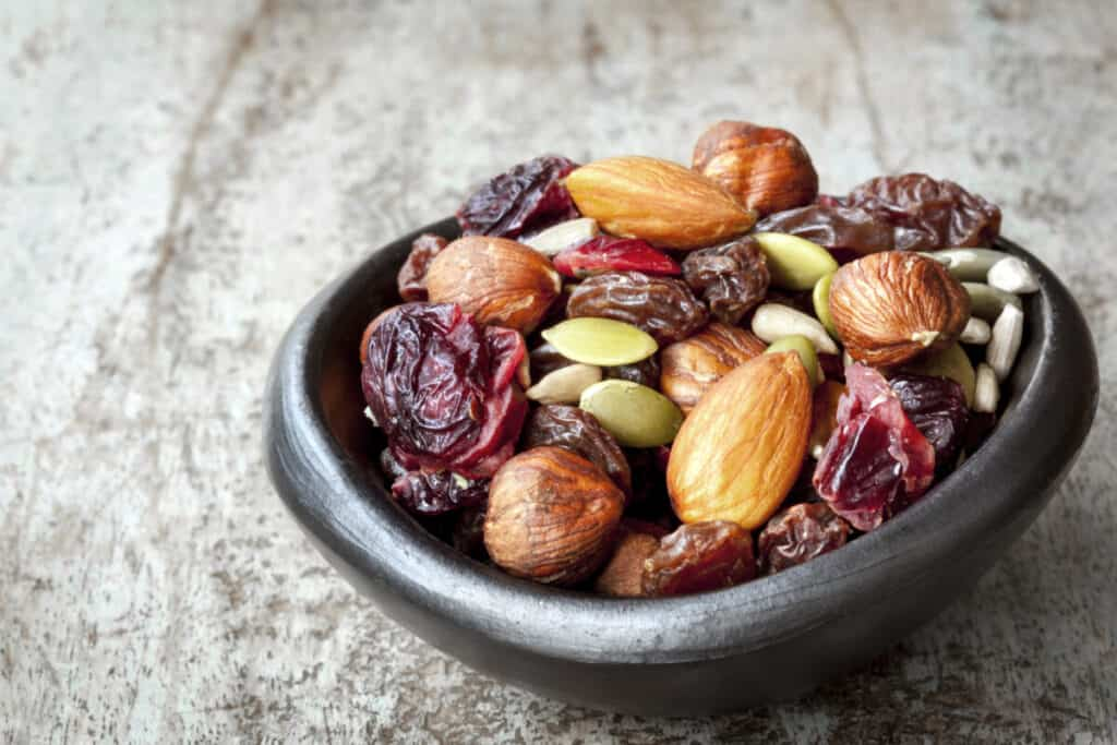 black-bowl-of-trail-mix-almonds-pumpkin-seeds-raisins-sunflower-seeds