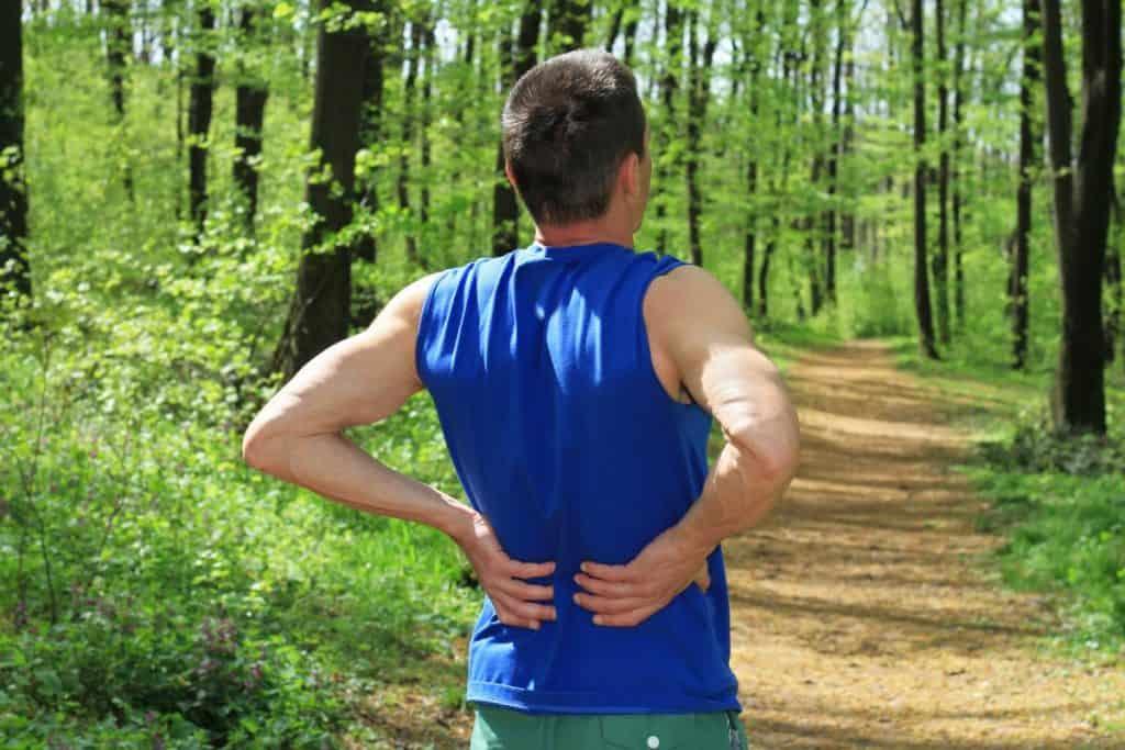 man-holding-lower-back-during-rest-during-jog